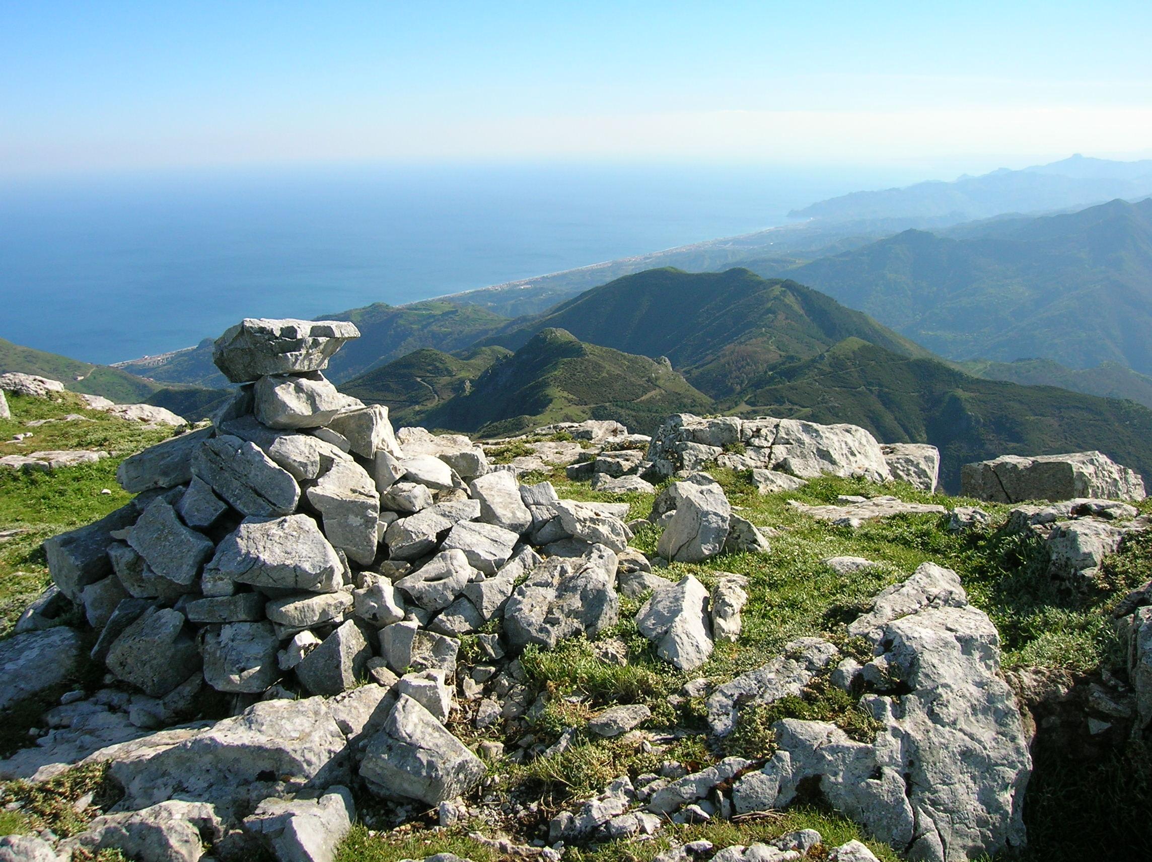 Auf dem mit Kalksteinen übersäten Hochplateau des Monte Scuderi markiert auf dem rechten südlicheren der beiden flachen Kuppen ein Steinhaufen den Gipfel, der Blick reicht bis weit über die Ostküste Siziliens
